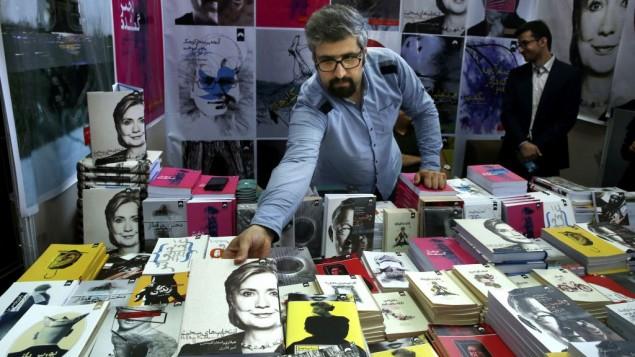 کتابفروش ایرانی در حال مرتب کردن نسخه فارسی کتاب «انتخاب های دشوار» هیلاری کلینتون در نمایشگاه بین المللی کتاب تهران است