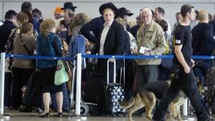 یک نگهبان فرودگاه اسرائیلی در حال گشت با سگ در فرودگاه بن گوریون در نزدیکی تل آویو، ۲۲ مارس ۲۰۱۶ (AP Photo/Ariel Schalit)