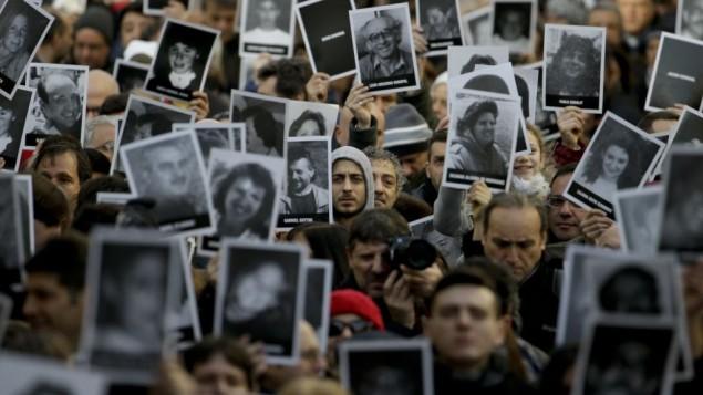 مردم عکس کشته شدگان را در بیست و دومین سالگرد بمب گذاری مرکز یهودیان آمیا سر دست بلند کرده اند