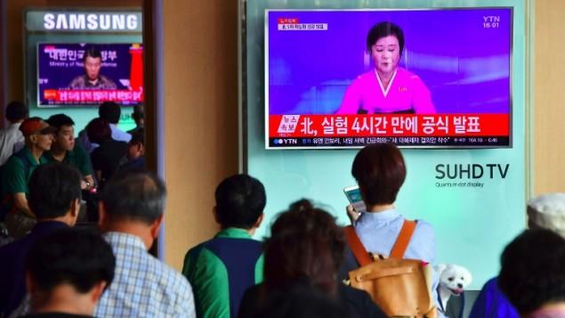 مردم در حال تماشای اخباری در یک ایستگاه ترن