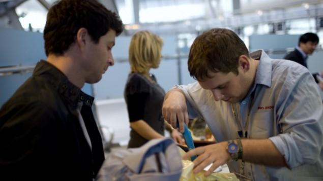 در فرودگاه بن گورین چمدان یکی از مسافران توسط کارمند امنیتی این فرودگاه بازرسی میشود