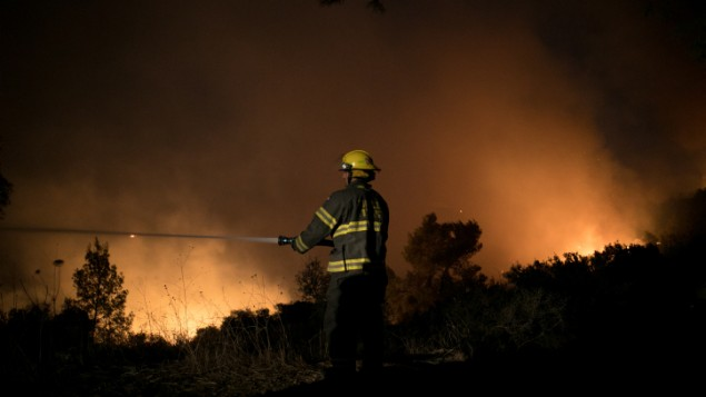 آتشنشانها در حال خاموشساختن آتشسوزی در ورودی شهرک نتاف