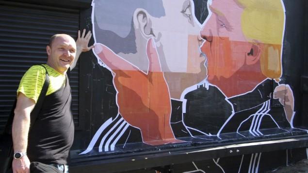 دومینیکاس سکاسکاس، مالک رستورانی در ویلنیوس پایتخت لیتوانی، ۱۳ می ۲۰۱۶ در کنار دیوارنگارهای بر دیوار رستوران وی که دونالد ترامپ و ولادیمیر پوتین رئیسجمهور روسیه را در حال بوسیدن یکدیگر نشان میدهد