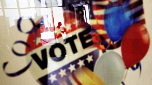 انعکاس تصویر یک رأیدهنده در شیشه قاب پوستر دیده میشود