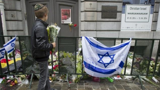 توضیح تصویر – یک پسر یهودی گلبهدست روبهروی پرچم اسرائیل و گلهایی که بیرون موزهی یهودی بروکلسل گذاشته شده (دو روز پیش از آن، تیراندازی مرگباری در همین محل روی داد)، ایستاده است. ۲۶ می ۲۰۱۴