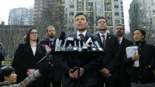 نوآ پورسل، معاون دادستان ایالت واشینگتن، (مرکز) پس از جلسهی دادگاه فدرال در سیاتل با گزارشگران سخن میگوید و باب فرگوسن، دادستان کل، (سوم از راست) نظاره میکند