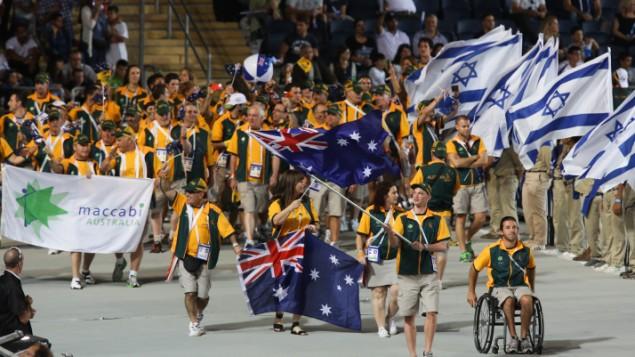 توضیح تصویر: ورزشکاران هیأت استرالیایی با پرچمهای ملی کشور خود در مراسم بازگشایی بازیهای مکابیا در اورشلیم اسرائیل، ۱۸ ژوئیه ۲۰۱۳