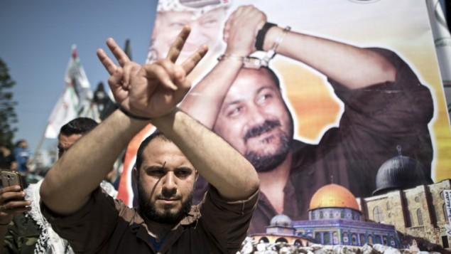 توضیح تصویر: مردی فلسطینی در مقابل پوستر رهبر زندانی فتح، مروان برقوتی، در تظاهرات روز زندانیان فلسطینی در شهر غزه، ۱۷ آوریل ۲۰۱۶، دستها را با ژست بالا برده