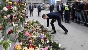 سیاستمدار سوسیال دموکرات آندراس یگیمن پای بنای موقت یابود، نزدیک محلی که کامیون، روز گذشته، بیرون یک فروشگاه زنجیرهای شلوغ در استکهلم، به میان جمعیت راند، دسته گل میگذارد، ۸ آپریل ۲۰۱۷