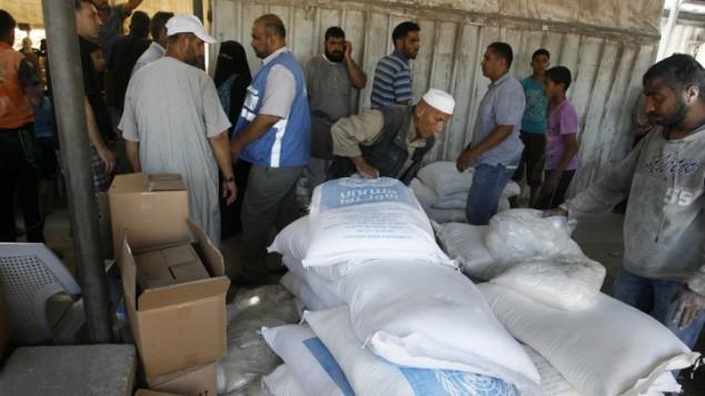توضیح تصویر: فلسطینیان در یکی از مراکز توزیع سازمان ملل در کمپ پناهندگی رفاه، جنوب نوار غزه، ۳۱ ژوئن ۲۰۱۴