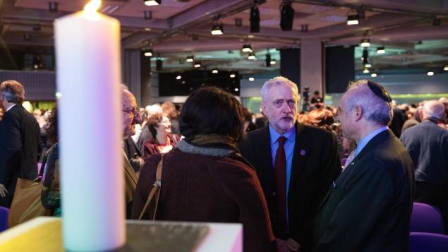 توضیح تصویر: جرمی کوربین، رهبر حزب کارگر، (دومی از راست) حین صحبت با مهمانان در مراسم بزرگداشت هولوکاست سالن کنفرانس ملکهی الیزابت دوم، ۲۶ ژانویه ۲۰۱۷، لندن، انگلستان