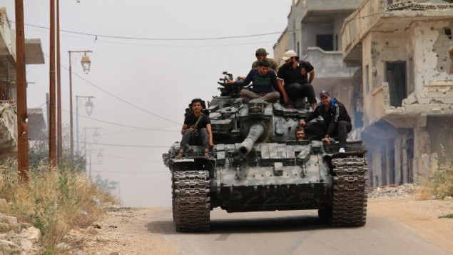 توضیح تصویر: رزمندههای اپوزیسیون در منطقهی تحت تصرف شورشیان در شهر درعه در جنوب سوریه، در زد و خوردهای تازه با نیروهای وفادار به رژیم، تانکی را در شهر میرانند – ۱۰ ماه مه ۲۰۱۶