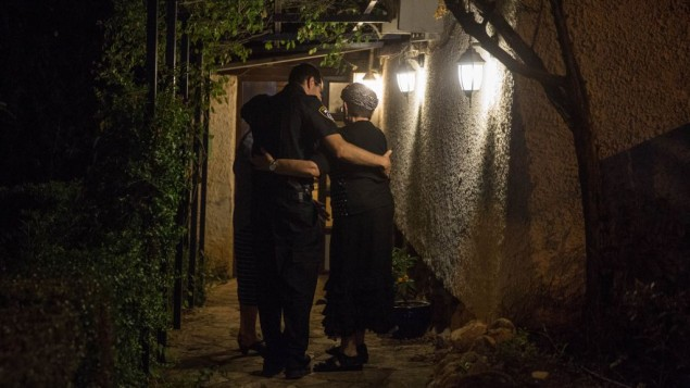 توضیح تصویر: یک پلیس دست دور کمر همسایهی سه اسرائیلی یک روز پیش از این به ضرب چاقو در شهرک هلامیش در کرانهی باختری کشته شدند، انداخته – شنبه ۲۲ ژوئیه ۲۰۱۷