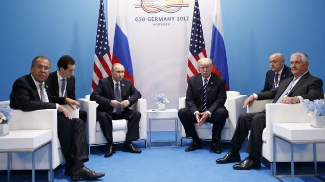 توضیح تصویر: در عکس ۷ ژوئیهی ۲۰۱۷، دونالد ترامپ رئیس جمهور ایالات متحده در ملاقات با ولادیمیر پوتین رئیس جمهور روسیه در نشست سران ج۲۰ دیده میشود، همراه با سرگئی لاوروف وزیر خارجهی روسیه سمت چپ، رکس تیلرسون وزیر خارجه ایالات متحده سمت راست.