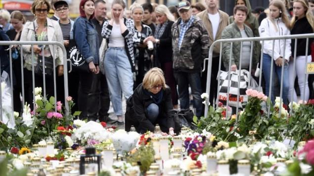 توضیح تصویر: مردم برای قربانیان چاقوزنی روز جمعه در میدان بازار شهر تورکو، در محل موقتی یادبود گل و شمع میگذارند – فنلاند ۱۹ اوت ۲۰۱۷