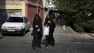 دو زن ایرانی چادری حین عبور از خیابانی در مرکز شهر تهران