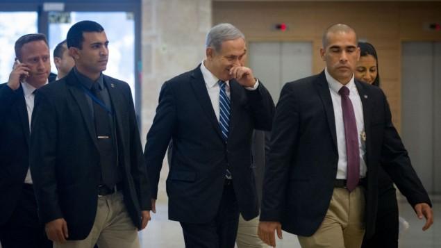 توضیح تصویر: بنیامین نتانیاهو، وسط، حین ورود به جلسهی لیکود در کنست به همراه دستیار، آری هارو، منتهای چپ، ۸ دسامبر ۲۰۱۴