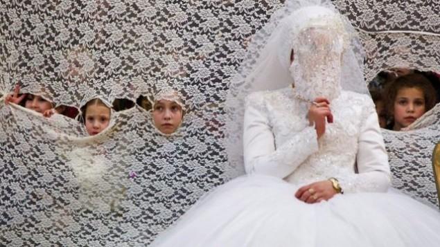 توضیح تصویر: عکس تزئینی – دخترکی جوان از پشت پردهی توری  کنار عروس،  در مراسم عروسی ارتدکس افراطی تماشا میکند – ۱۸ ژانویه ۲۰۱۶