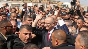 رامی حمدالله (وسط) نخست وزیر تشکیلات خودمختار فلسطینی در حلقهی ماموران امنیتی هنگام ورود به گذرگاه مرزی ارز در بیت حانون، شمال نوار غزه برای هواداران دست تکان میدهد – ۲ اکتبر ۲۰۱۷