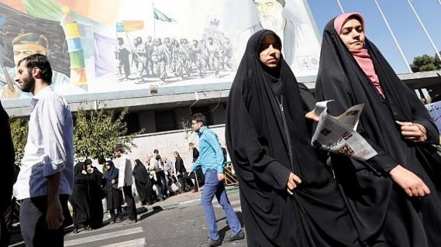 چند زن ایرانی ، پس از نماز جمعه، حین عبور از خیابانی در تهران، با تصویری از ولی فقیه پیشین آیتالله روحالله خمینی در زمینهی عکس – ۱۳ اکتبر ۲۰۱۷