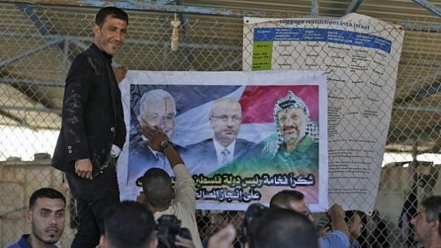 مردان فلسطینی پوستری از محمود عباس رهبر فلسطینی (چپ)، رامی حمدالله نخست وزیر، و یاسر عرفات رهبر فقید در دروازهی شهر شمالی نوار غزه، درست بعد از گذرگاه تحت کنترل اسرائیل، ارز، به نمایش گذاشتهاند