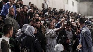 فلسطینیها با مقامات حماس و نیروهای امنیتی در یکی از ترمینالهای موقت در یک زمین بسکتبال در خان یونیس، جنوب نوار غزه، ۱۸ نوامبر ۲۰۱۷، در حالی که منتظر تأیید مدارکاند تا با اتوبوس از مرز رفاح به مصر بروند