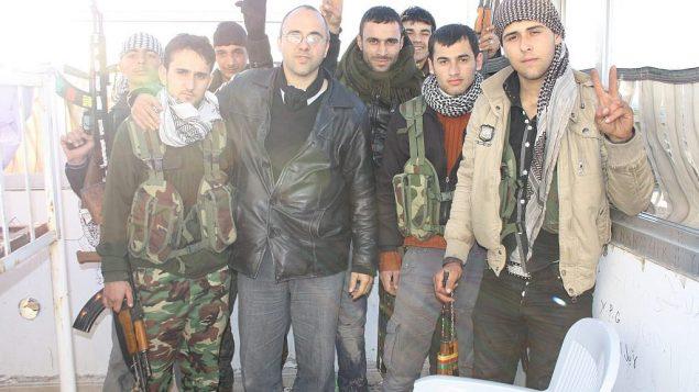 توضیح تصویر: جاناتان اسپایر با کت چرمی سیاه، در دیدار با رزمندههای وایپیجی کورد در سوریهی شمالی – ۲۰۱۳
