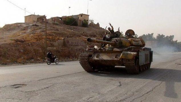 توضیح تصویر: رزمندهی هوادار رژیم، ۲۱ اوت ۲۰۱۶ حین عبور با تانک در ناحیهی جنوبی قویران، شمال غربی سوریه، شهر حصارک، که نیروهای کورد در حال پیشرفت هستند، با علامت پیروزی عبور میکند