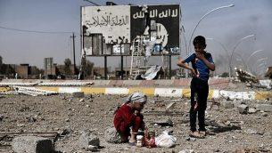 توضیح تصویر: در عکس ۱۲ مارس ۲۰۱۷ کودکان عراقی در میانهی خرابههای خیابانی در محلهی نبولوس موصل در مقابل بیلبوردی با لوگوی داعش نشستهاند و همزمان نیروهای امنیتی برای بازپسگیری بخشهای غربی شهر از داعش، حمله کردهاند