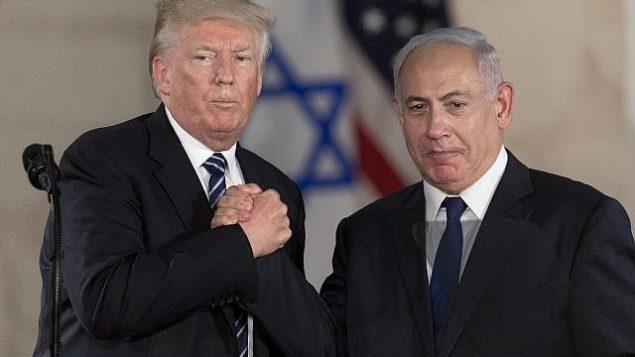 توضح تصویر: بنیامین نتانیاهو نخست وزیر، راست، و دونالد ترامپ رئیس جمهور ایالات متحده حین دست دادن در موزهی اسرائيل در اورشلیم، ۲۳ مه ۲۰۱۷
