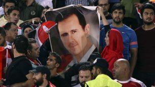 هواداران سوری فوتبال پوستر رئیس جمهور بشار اسد را پیش از شروع دور سوم بازی با ایران – بازیهای مقدماتی جام جهانی در استادیوم آزادی تهران، ایران – ۵ سپتامبر ۲۰۱۷ (عکس: (AP Photo/Vahid Salemi