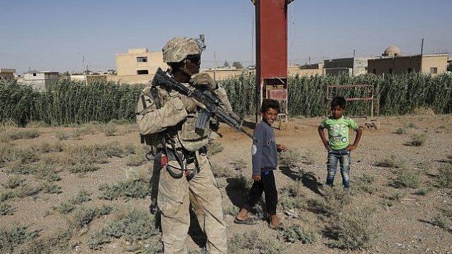 توضیح تصویر: یک سرباز آمریکا در جادهای که به رقهی سوریه میرود، در نزدیکی چند کودک ایستاده است – ۲۶ ژوئیه ۲۰۱۷