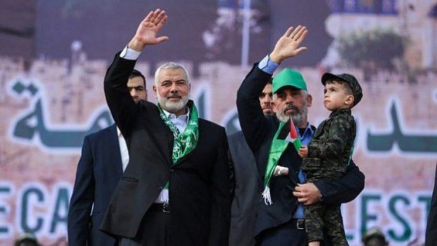 توضیح تصویر: اسماعیل هنیه رهبر حماس (چپ) و یحیی سینوار رهبر حماس در نوار غزه در راهپیمایی سیزدهمین سالگرد بنیانگزاری جنبش تروریستی در شهر غزه برای جمعیت دست تکان میدهند – ۱۴ دسامبر ۲۰۱۷