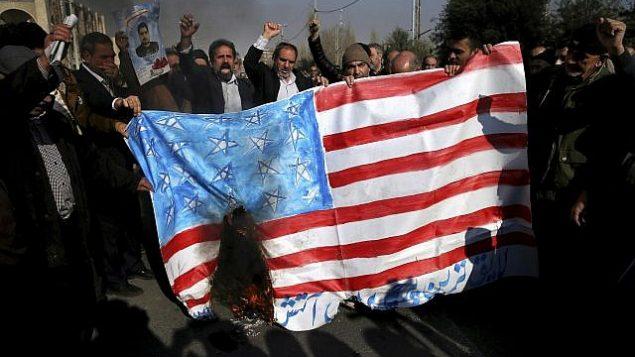 توضیح تصویر: نمازگزاران ایرانی حین شعار و سوزاندن نماد پرچم ایالات متحده در یکی از راهپیماییها علیه معترضین ضددولتی پس از نماز جمعهی تهران، ایران – ۵ ژانویه۲۰۱۸