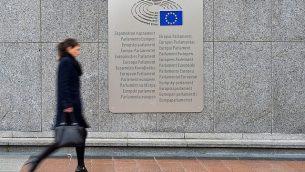توضیح تصویر: زنی از کنار پلاکاردی با عباراتی که پارلمان اروپا به زبان کشورهای عضو بیرون از اسپیس لئوپولد در ۲۵ فوریه ۲۰۱۶ در بروکسل، بلژیک قرار داده، عبور میکند.  (Ben Pruchnie/Getty Images via JTA)