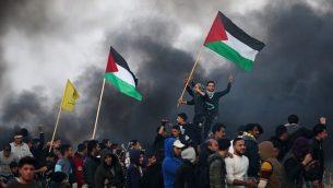 توضیح تصویر: تزئینی، معترضین فلسطینی با پرچم ملی حین زدوخورد با مأموران امنیتی اسرائیلی در حومهی شرقی شهر غزه، نزدیک مرز اسرائیل، ۱۲ ژانویه ۲۰۱۸. (AFP Photo/Mohammed Abed)