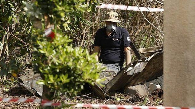 توضیح تصویر: عکسی که ۱۰ فوریه ۲۰۱۸ در دشت جزریل در شمال اسرائیل گرفته شده کارشناسان بمب را در حال وارسی خردهپارهها. (AFP PHOTO / Jack GUEZ)
