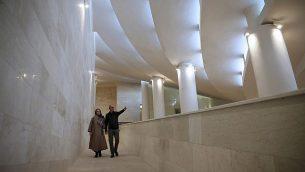 توضیح تصویر: ۷ فوریه ۲۰۱۸، رضا دانشمیر، راست، حین گفتگو با همسر خود کاترین اسپیریدونوف، هر دو آرشیتکتهای مسجد ولی عصر، در حال عبور از یکی از سربالاییهای مسجد، تهران، ایران. (AP Photo/Vahid Salemi)