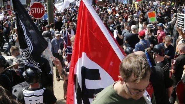 توضیح تصویر: یک نژادپرست سفید در حال حمل پرچم نازیها به داخل پارک ایمنسیپیشن در شارلوتزویل، ویرجینیا، ۱۲ اوت ۲۰۱۷ . (AP/Steve Helber)