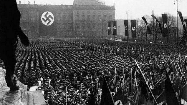توضیح تصویر: عکسهای اسوشیتد پرس از ۱۱ فوریه  ۱۹۳۶، جشنهایی که در سراسر آلمان در استقبال از سومین سالگرد روی کار آمدن ناسیونال سوسیال ها (نازی ها) برگزار شد؛ سوسیالیسم ملیگرا در ۱۹۳۳ در آلمان به قدرت رسید. ظهر آن روز، آدولف هیتلر ۲۵هزار تن از رفقای قدیمی استورمتروف خود را در لوستگارتن برلین گرد هم آورد. ضمن سخنرانی خود، هیتلر بر ارادهی مبتنی به صلح آلمان تاکید کرد. این منظری عمومی از پرچمدارها و پارچهنوشتهدارها حین راهپیمایی در برلین است.  (AP Photo)