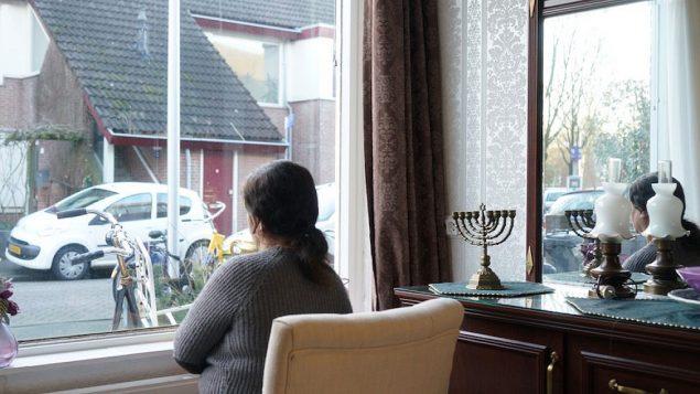 توضیح تصویر: صفورا، پناهجوی یهودی ایرانی، از پنجرهی خانهی دخترش در هلند به بیرون نگاه میکند، ۱۵ فوریه ۲۰۱۸. (Cnaan Liphshiz)