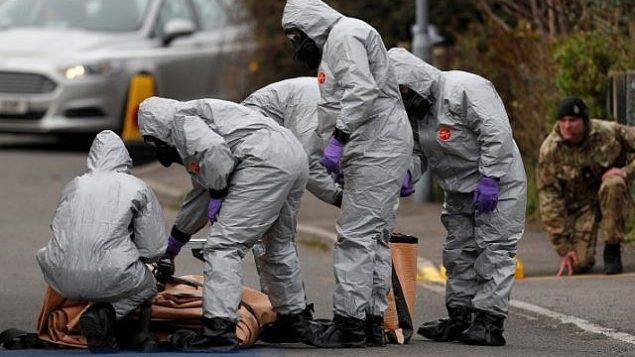 توضیح تصویر: کارکنان نظامی بریتانیا با یونیفرمهای محافظ میکوشند خودرویی مرتبط با حملهی گاز اعصاب سالیسبوری، جنوب شرقی انگلستان، در ۴ مارس ۲۰۱۸ را از صحنه خارج کنند. (Adrian DENNIS/AFP)
