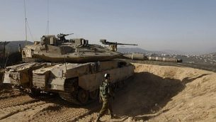 عکسی از ۱۶ نوامبر ۲۰۱۷ یک سرباز اسرائیلی را نشان میدهد که در کنار تانک در یک موضع نظامی مشرف به جنوب لبنان در شهر شمالی اسرائیل، متولا، در امتداد مرز اسرائیل با لبنان قدم میزند.  (AFP PHOTO / MENAHEM KAHANA)