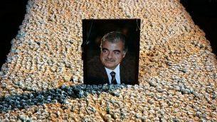 توضیح تصویر: پرترهی رافیک حریری نخست وزیر مقتول لبنان بر مقبرهی پوشیده از گل در مرکز شهر بیروت، لبنان، ۱۵ ژانویه ۲۰۱۴. (AP/Hussein Malla)