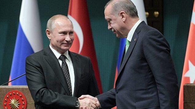 توضیح تصویر: ولادیمیر پوتین پرزیدنت روسیه، چپ، رجب طیب اردوغان پرزیدنت ترکیه پس از کنفرانس مطبوعاتی طی ملاقات این دو در آنکارا، دست میدهند، ترکیه، ۱۱ دسامبر ۲۰۱۷. (Alexei Druzhinin/Pool Photo via AP)