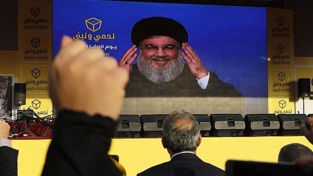 توضیح تصویر: حسن نصرالله رهبر حزب الله حین ایراد سخنرانی تلویزیونی بر صفحهای عظیم هنگام کارزار انتخاباتی در حومهی جنوبی بیروت، لبنان، ۱۳ آوریل ۲۰۱۸. (AP Photo/Hussein Malla)