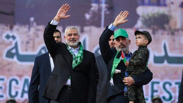 توضیح تصویر: اسماعیل هانیه، چپ، و یحیی سینوار رهبر حماس در نوار غزه، در راهپیمایی سالگرد سی سالگی تأسیس جنبش تروریستی به جمعیت دست تکان میدهند، باریکه غزه، ۱۴ دسامبر ۲۰۱۷.  (Mohammed Abed/AFP)