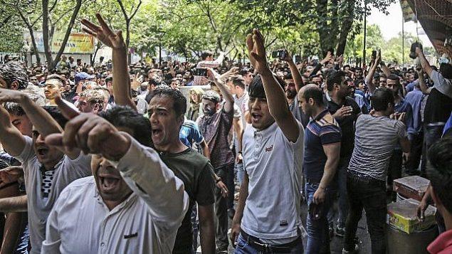 توضیح تصویر: گروهی از تظاهرکنندگان حین شعار دادن