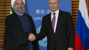 توضیح تصویر: ولادیمیر پوتین رئیس جمهور روسیه، راست، و حسن روحانی رئیس جمهور ایران حین ملاقات در کینگداو، چین، دست میدهند، شنبه ۹ ژوئیه ۲۰۱۸.  (AP Photo/Alexander Zemlianichenko, Pool)