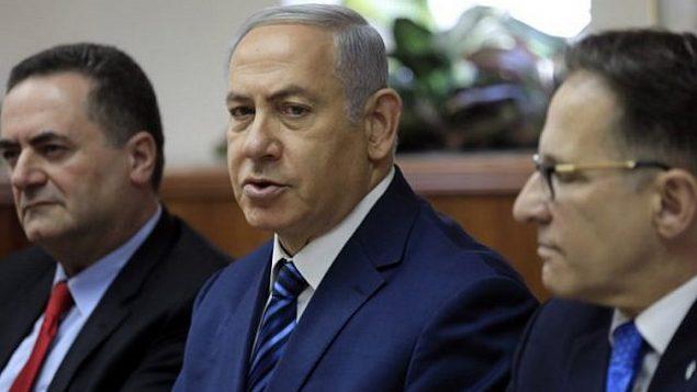 توضیح تصویر: بنیامین نتانیاهو، وسط، در رأس جلسهی هفتگی کابینه در دفتر خود در اورشلیم، ۱ ژوئیهی ۲۰۱۸، در میان زاخای براورمن منشی کابینه، راست، و یسرائیل کاتز وزیر اطلاعات و ترابری، چپ.  (AFP PHOTO / POOL / Tsafrir Abayov)